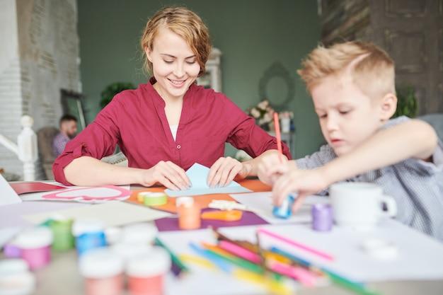 彼の母親の隣に絵を描く少年