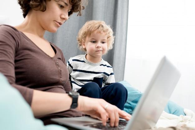 ラップトップを使用してママを見て少年