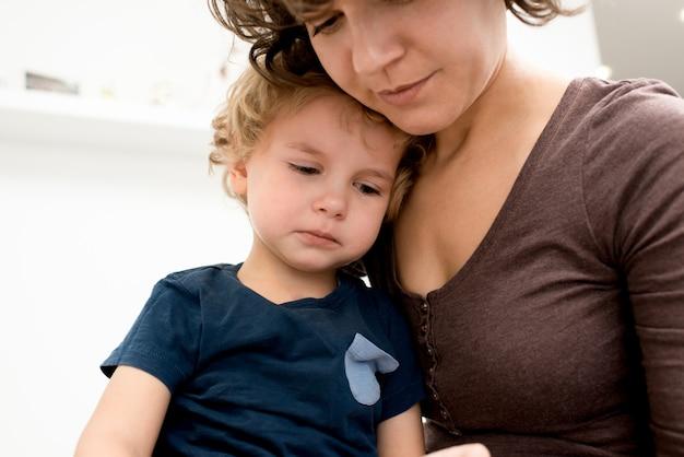 Мать успокаивает плачущего сына