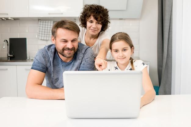 キッチンでラップトップを使用して家族
