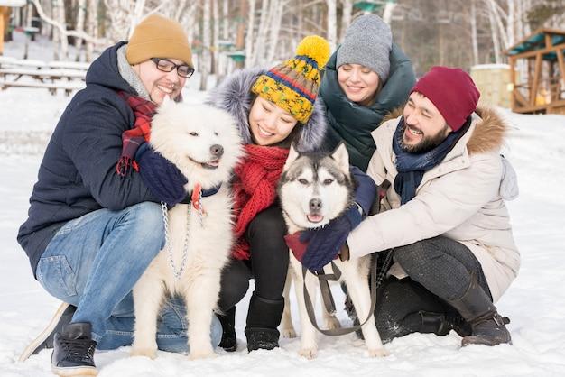 Молодые люди позируют с чистокровными собаками