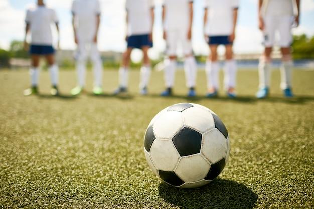 ジュニアサッカーの試合で草の上にボール