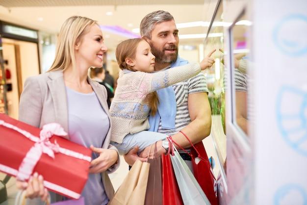 モールで店の窓を探索する両親を持つ少女