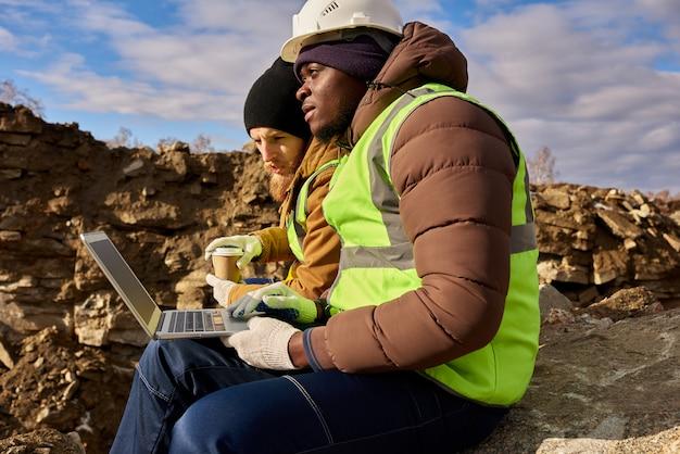 採掘現場でラップトップを使用する鉱山労働者