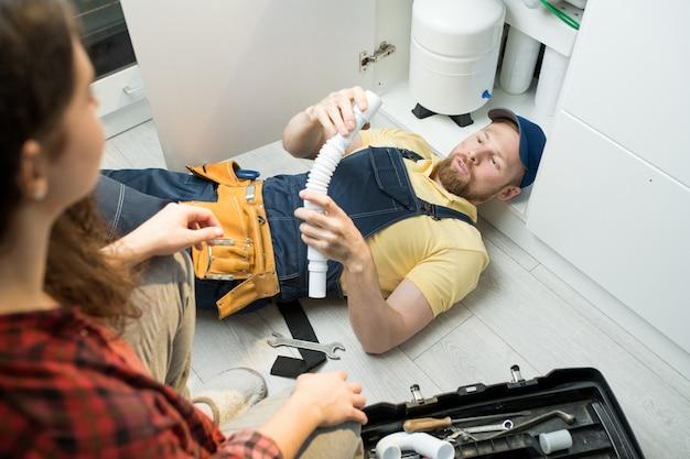 Молодой сантехник меняет ловушку под раковиной