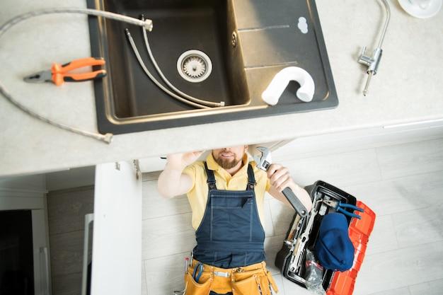 Сантехник ремонтирует трубы на кухне