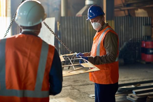 Рабочие фабрики, использующие подъемную балку