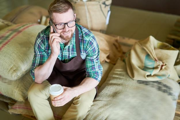 Бариста сидит на пакетиках с кофе