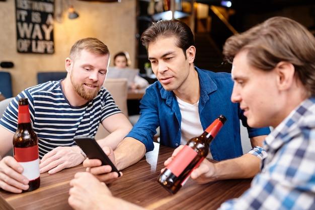 Любопытные люди читают новости по телефону и вместе пьют пиво