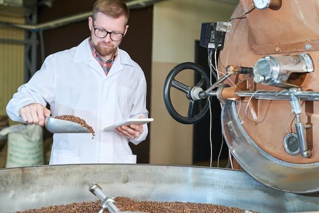 Рабочий проверяет качество обжарки кофе
