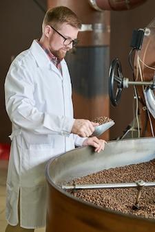 Молодой человек обжаривает кофе на фабрике