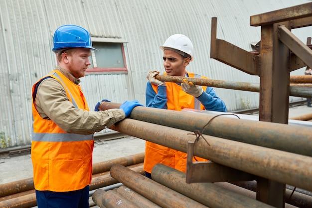 Рабочие, двигающие трубы