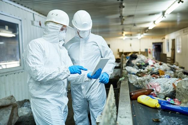 Два рабочих на современном заводе по переработке