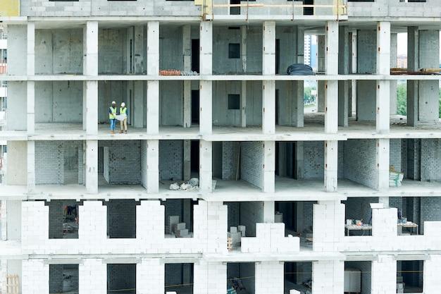 Строительные рабочие на стройке жилого дома