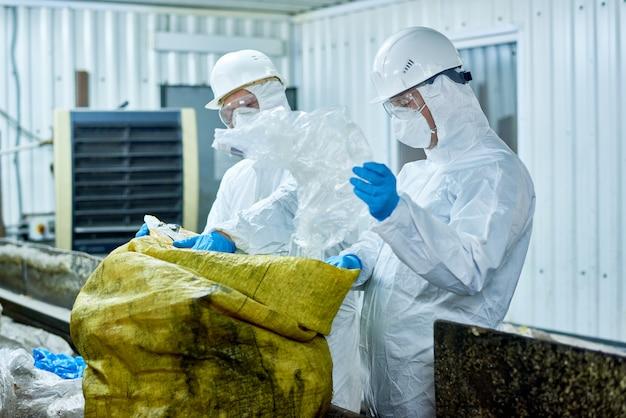 ゴミのリサイクルプラントでプラスチックを選別する労働者
