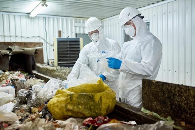 コンベヤーベルトでゴミを選別する労働者