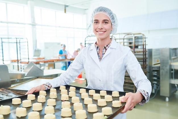 Женский пекарь держит интервал с пирожными