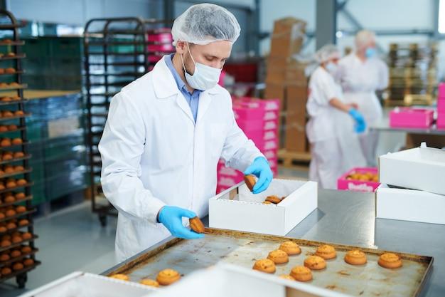 菓子工場労働者がペストリーをボックスに梱包