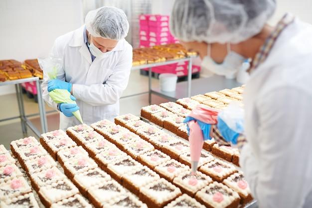 Кондитеры, украшающие торты кремом