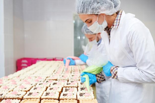 Вид сбоку профессиональных пекарей, вызывающих заварной крем