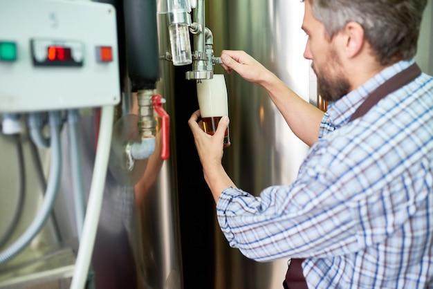 Современный пивовар наливая свежее пиво в стекло на заводе