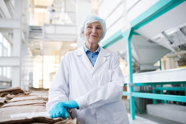 : старшая женщина позирует на заводе по переработке