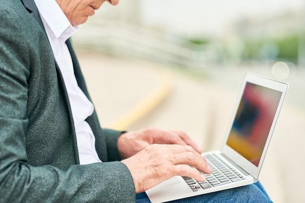 Пожилой бизнесмен с ноутбуком на лестнице