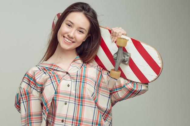 Классная студентка в повседневной одежде учится кататься на скейтборде после занятий в университете.