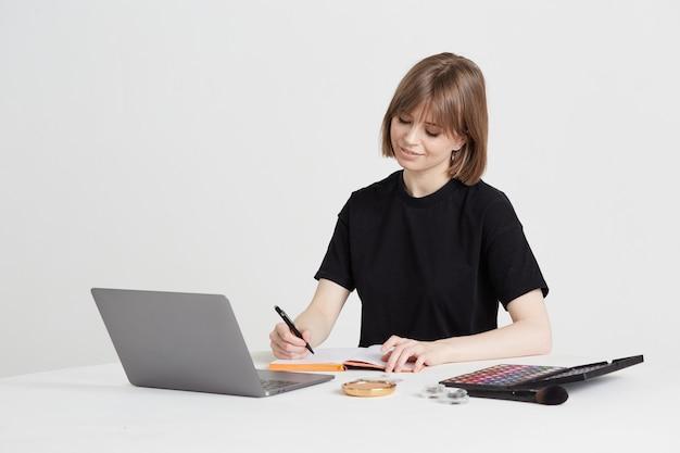 Милая молодая женщина изучает искусство макияжа удаленно, используя ноутбук и видеозвонки, через интернет, сидя дома.