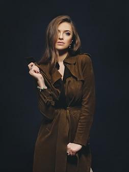 Студийный портрет молодой фотомодель в пальто с темной стеной на заднем плане