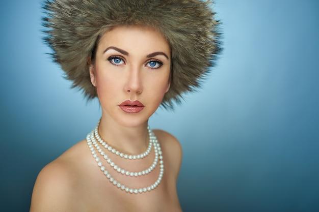 Портрет девушки в зимней шапке в студии на синем