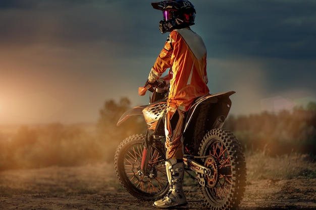 Вид сзади профессионального мотоциклиста готовится перед поездкой в горы, а затем на бездорожье. это закат.