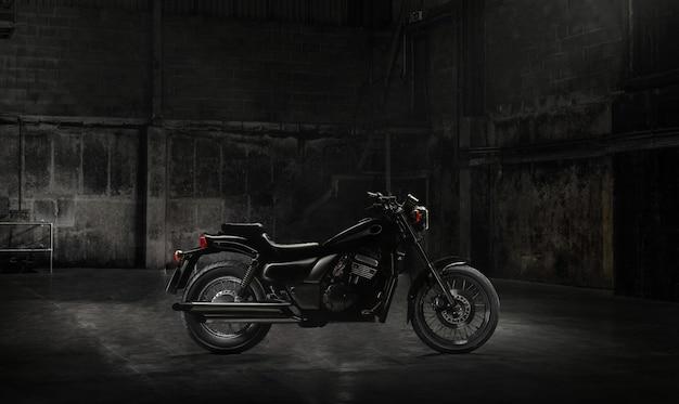 日光の光線で暗い建物に立っているビンテージバイク。側面図