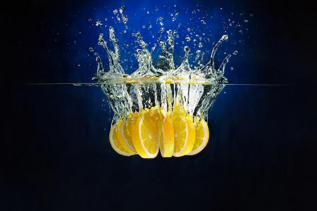 深い青色の背景にレモンのかけらが水に投げ込まれました。水中撮影。