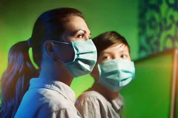 伝染性のコロナウイルスから身を守ろうとする、保護マスクを被った母親と息子の肖像画。