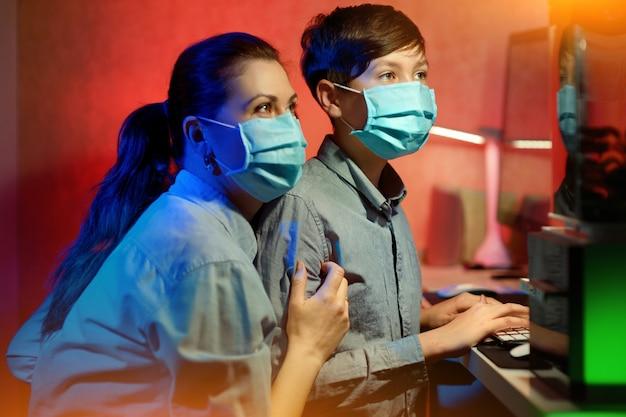 伝染性のコロナウイルスから身を守ろうとする、保護マスクを被った母親と息子の肖像画。コンピュータでオンラインレッスンを学びます。