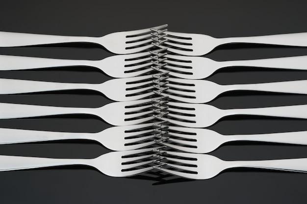 Набор серебряных, блестящих вилок, расположенных симметрично на черной зеркальной стене.