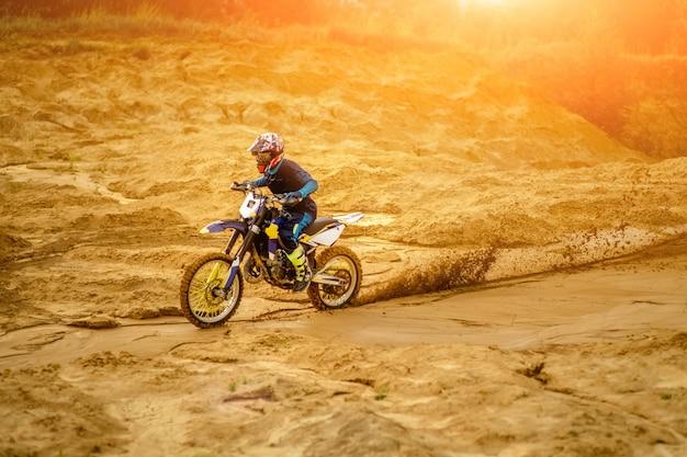 砂漠を走り、オフロードトラックをさらに下るオートバイライダー