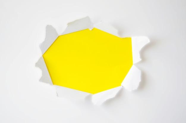 テキストの黄色の背景に引き裂かれた側面の小さな紙の穴。広告、印刷、または宣伝用コンテンツ用のテンプレート。