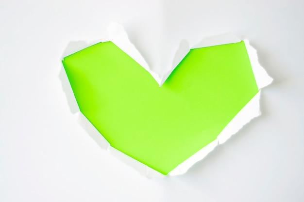 コピースペースの白い背景の上のハートの形で引き裂かれた側面を持つ緑の紙の穴。広告、印刷、またはプロモーションコンテンツのテンプレート。