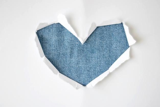 コピースペースの白い背景の上のハートの形で引き裂かれた側面を持つジーンズ繊維穴。広告、印刷、またはプロモーションコンテンツのテンプレート。