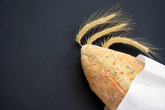 黒い黒板に小麦の穂でおいしい焼きたてのパン。ベーカリーやキッチンのコンセプトです。トップビューフラットレイアウト
