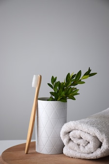 竹の歯ブラシと木製の丸いボードに白い巻きタオル