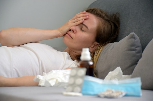 目を閉じて疲れている病気の女性は灰色のソファーで頭の痛みに苦しみ、フォアグラウンドで薬を手で彼女の頭に触れます。脱力感、うつ病、精神疾患、痛み、ストレスの概念