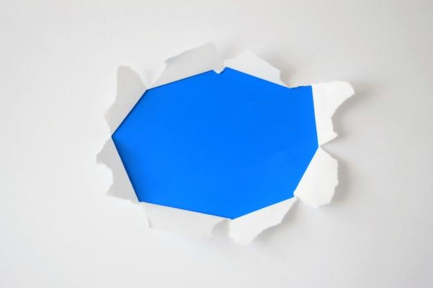 テキストの青い背景に引き裂かれた側面の破れた紙の穴。広告、印刷、またはプロモーションコンテンツ用のテンプレート。