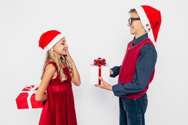 幸せな少女と少年のサンタ帽子、スタイリッシュな兄と妹
