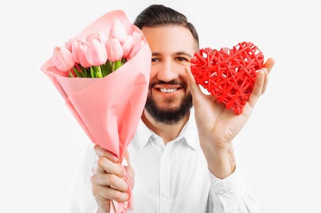 ピンクのチューリップの花束と赤いバレンタインハートのひげを持つエレガントな男、バレンタインデーのギフト