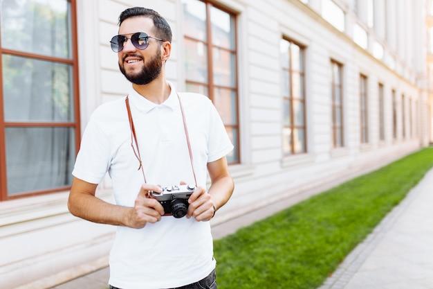 Стильный хипстер с бородой и камерой, гуляя по городу с камерой,
