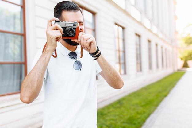 Стильный хипстер с бородой и фотоаппаратом, фотографирует, гуляет по городу