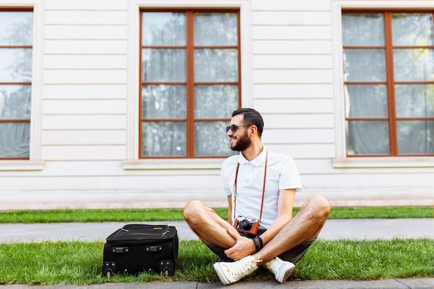 Стильный хипстер с чемоданом и камерой сидит на газоне в парке
